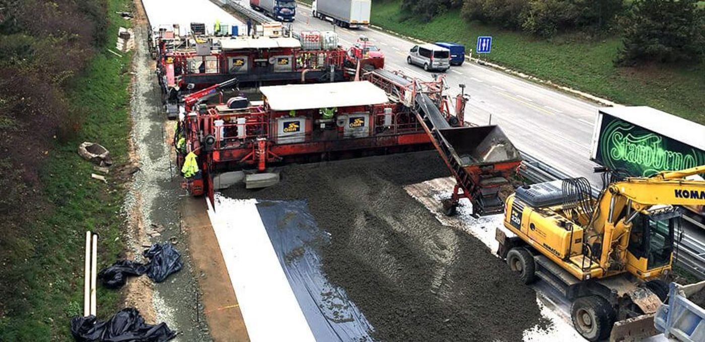 Photo: Two OEBA concrete pavers concreting the left-hand section of the Czech D2, heavy traffic on all three lanes of the right-hand part of the roadway
