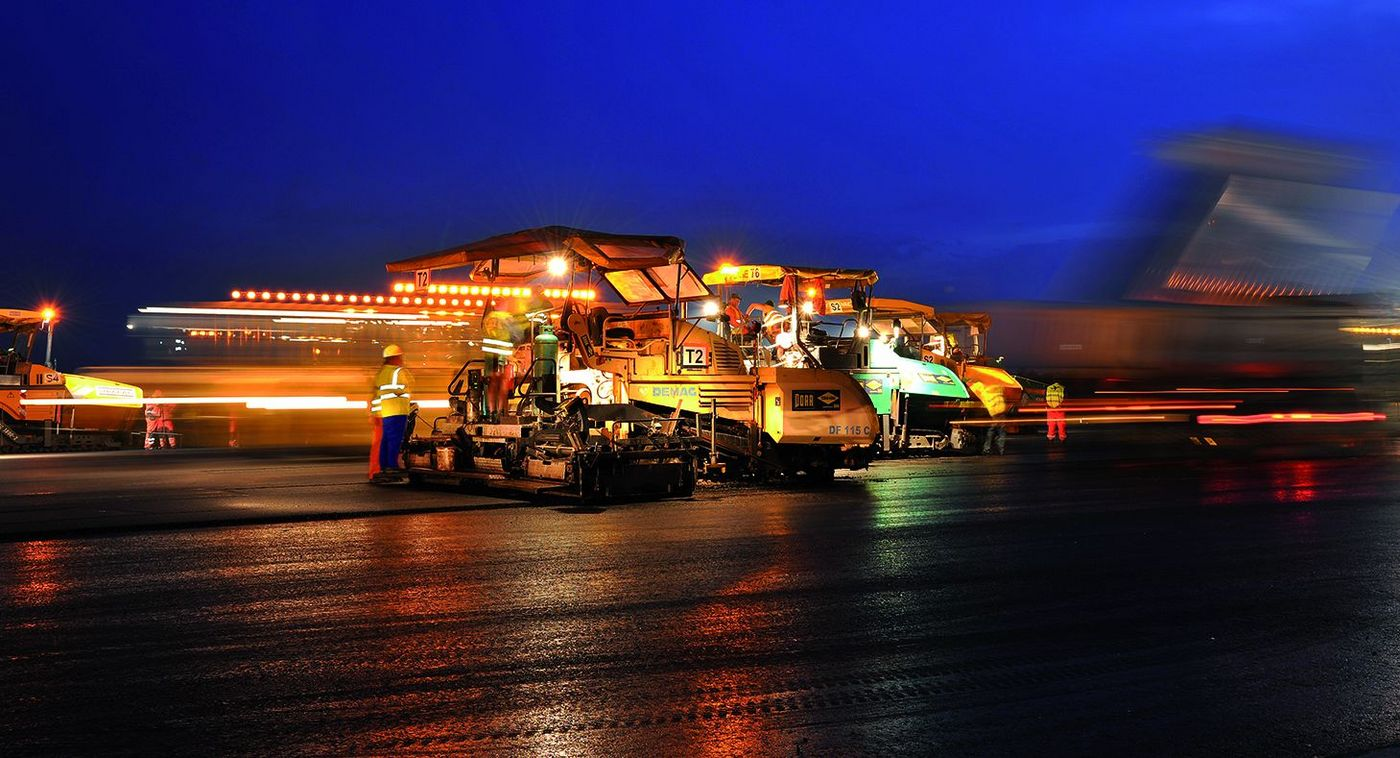 Photo: Runway renovation at Vienna Airport: Construction vehicles on the airfield, illuminated against the night sky.
