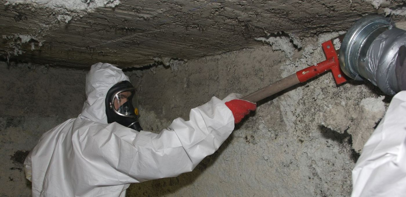 Photo: Asbestos rehabilitation: A worker wearing full body protection and a respiratory mask removes the coating from a building section.