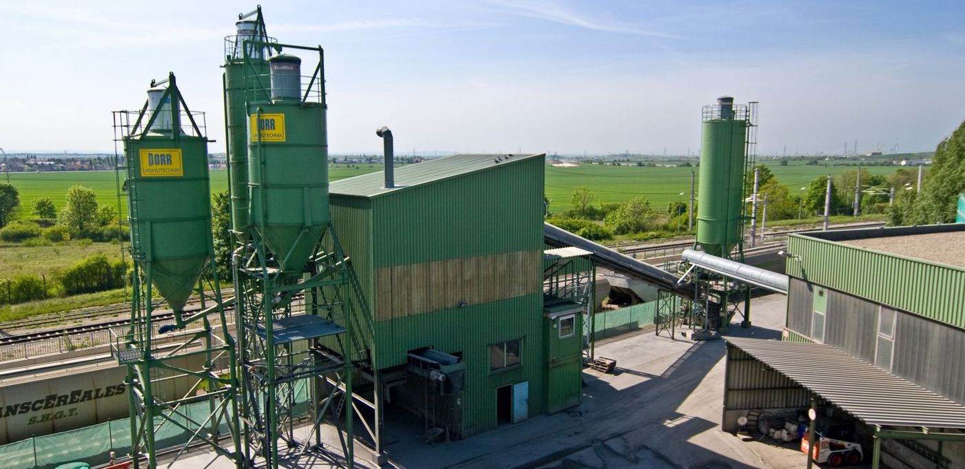 Photo: Stabilising system: industrial plant painted in green with silos and two buildings connected to one another through conveyor belts