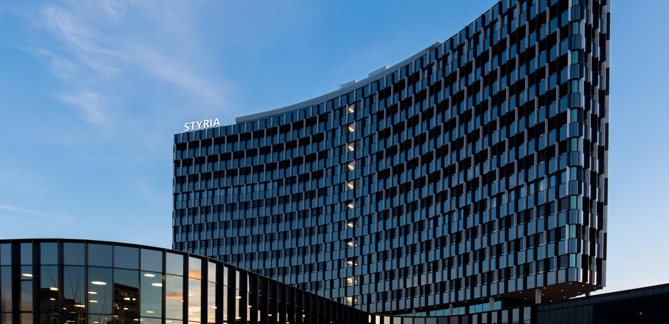 Photo: Styria Media Center: Evening atmosphere, the high-rise building's curved glass façade and a glazed low-rise building in the foreground